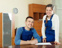Happy smiling young workers in uniform with financial documents. At table royalty free stock photos
