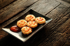 Happy snack with Chicken nugget with smile tomato sauce in black plate on rough wooden Royalty Free Stock Images