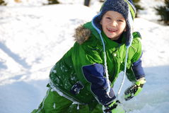 Happy snow boy. A boys looks happy playing in snow Royalty Free Stock Photos