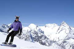 Happy snowboarder. On slope of Caucasus Mountains. Winter resort Dombaj Stock Photo