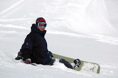 Happy snowboarder 2. Happy snowboarder sitting on the snow royalty free stock photo