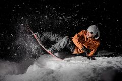 Happy snowboarder in orange jacket with stuck out tongue riding. Happy snowboarder in orange jacket riding with stuck out tongue on a snowy powder hill at dark royalty free stock photos