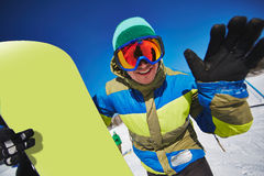 Happy snowboarder. Young sportsman with snowboard looking through eyeglasses at winter resort Royalty Free Stock Images