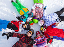 Happy snowboarders lying in circle lifting hands Royalty Free Stock Photos