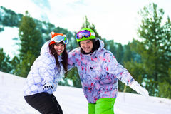 Happy snowboarders try to balance and laugh Stock Photos