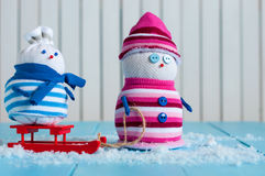Happy snowman couple in winter sitting with a sled Royalty Free Stock Photography