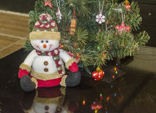 Happy snowman doll. Sitting under the Christmas tree Royalty Free Stock Photo