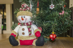 Happy snowman doll. Sitting under the Christmas tree Royalty Free Stock Photography