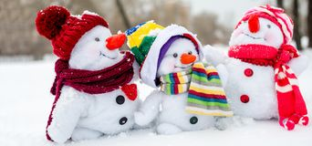 Happy snowman family. With hats n the snow Royalty Free Stock Image