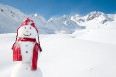 Happy snowman in mountains Stock Images