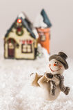 Happy snowman next to a house. Happy snowman playing with snow on white background Stock Photography