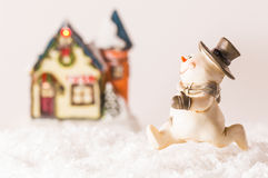 Happy snowman next to a house. Happy snowman running home on white background Royalty Free Stock Photo