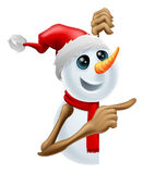 Happy snowman in Santa hat pointing Royalty Free Stock Images