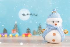 Happy snowman standing in blue winter christmas snow background. Merry christmas and happy new year greeting card with copy-space. Royalty Free Stock Photo