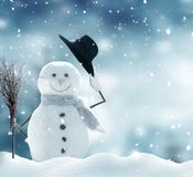 Happy snowman  standing in winter Christmas landscape. Stock Photo