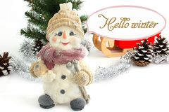Happy snowman surrounded by pine cones. Snowman with Santa`s sleigh. stock image