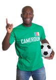 Happy soccer fan from Cameroon with ball. Laughing at camera on an isolated white background for cutout Stock Images