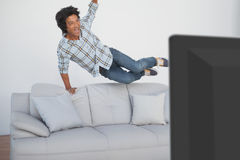 Happy soccer fan cheering while watching tv. Portrait of a happy soccer fan cheering while watching tv Stock Photo