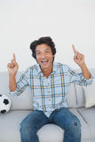Happy soccer fan cheering while watching tv. Portrait of a happy soccer fan cheering while watching tv Stock Photography