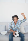 Happy soccer fan cheering while watching tv. Portrait of a happy soccer fan cheering while watching tv Royalty Free Stock Photo