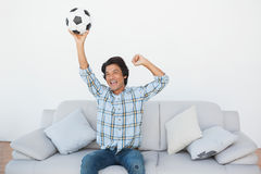 Happy soccer fan cheering while watching tv Royalty Free Stock Photography