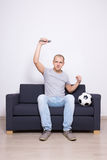 Happy soccer fan watching game on tv. Happy soccer fan watching game on television Royalty Free Stock Photography