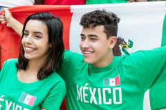 Happy soccer fans from Mexico with mexican flag. Outdoors at stadium stock image