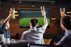 Happy soccer fans. Three friends watching a game at the pub.  Royalty Free Stock Photography