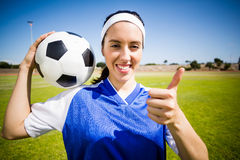Happy soccer player holding a ball and showing her thumbs up Royalty Free Stock Images
