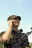 Happy soldier. Young soldier calling on a phone and smiling stock image