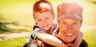 Happy soldier giving piggyback to his son. Portrait of happy soldier giving piggyback to his son in the park on a sunny day Royalty Free Stock Photography
