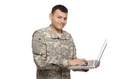 Soldier typing lon laptop Royalty Free Stock Photography