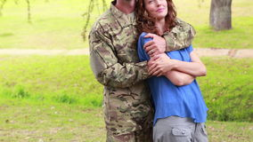 Happy soldier hugging his wife. In park stock footage