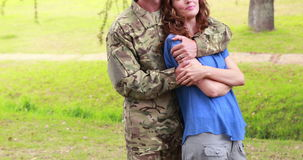 Happy soldier hugging his wife. In park stock video