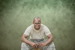 Happy soldier man sitting against green background Royalty Free Stock Photo