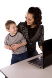 Happy son. A mom holding her son while trying to work on her computer, smiling at eachother Stock Images