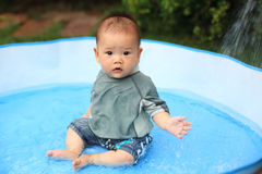 Happy son baby in inflatable pool Stock Image