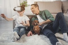 Happy son and dad entertaining with modern device at home. Joyful boy is watching video on virtual reality headset. His father and dog are sitting on floor next royalty free stock image