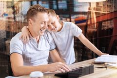 Happy son embracing his father. Friendly atmosphere. Positive delighted young men keeping smile on his face and leaning elbows on table while using his gadget Stock Photo