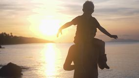 Happy son in eyeglasses sits on the shoulders of his father on tropical beach at stunning sunset in slow motion. Happy son in eyeglasses sits on the shoulders of stock video footage