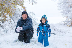 Happy son and father having fun with snow in. Winter portrait of kid boy and father in colorful clothes, outdoors during snowfall. Active outoors leisure with Royalty Free Stock Images