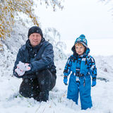 Happy son and father having fun with snow in winter. Winter portrait of kid boy and father in colorful clothes, outdoors during snowfall. Active outoors leisure royalty free stock photos