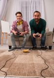 Happy son and father playing video game together. Teenage boy and father sitting on couch holding joysticks Stock Images
