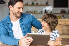 Happy son and father using tablet. In cafe royalty free stock photos