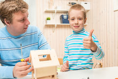 Happy son happy building bird feederstogether. With his father Royalty Free Stock Photos