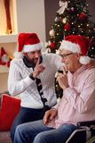 Happy son and his elderly father confessing a secret to each ano. Ther on Christmas eve royalty free stock images