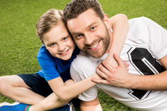 Happy son hugging smiling father while lying on grass. Portrait of happy son hugging smiling father while lying on grass Royalty Free Stock Photo