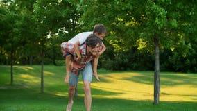 Son jumping on father back in green park. Joyful man giving boy piggyback riding