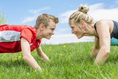 Happy son and mother are doing exercises in the summer park. A Happy son and mother are doing exercises in the summer park Stock Image