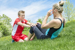 Happy son and mother are doing exercises in the summer park. A Happy son and mother are doing exercises in the summer park Royalty Free Stock Photography
